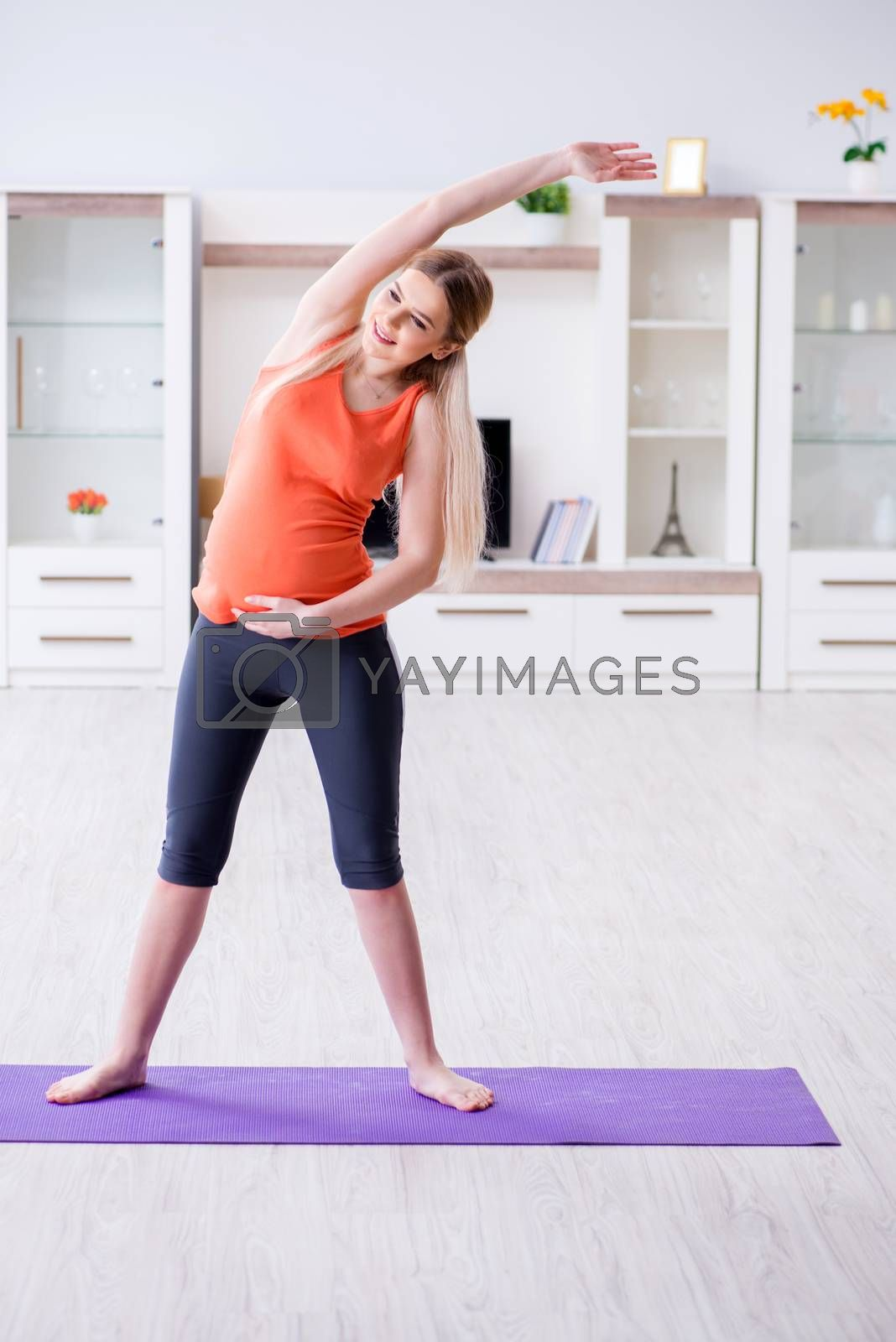 Pregnant woman doing sport exercise at home