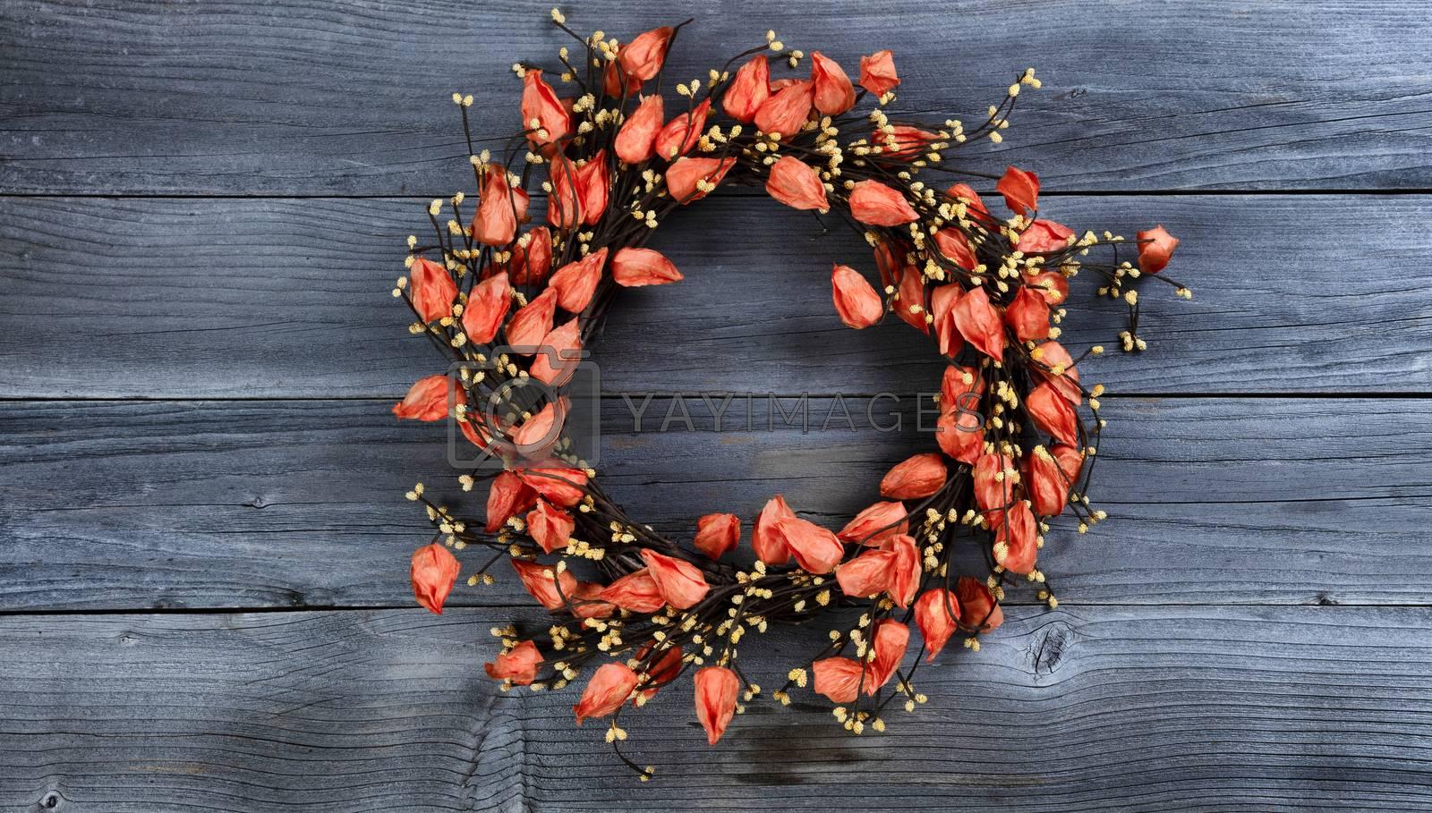 Seasonal autumn wreath with orange bell flowers on vintage wooden background
