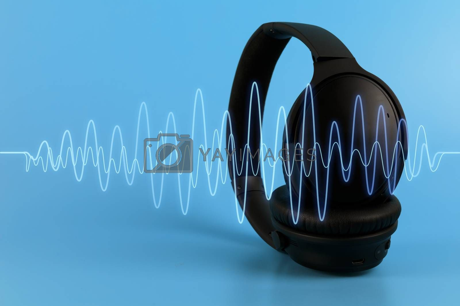 Black music headphones with blue sound wave on blue background. Multimedia concept with copy space