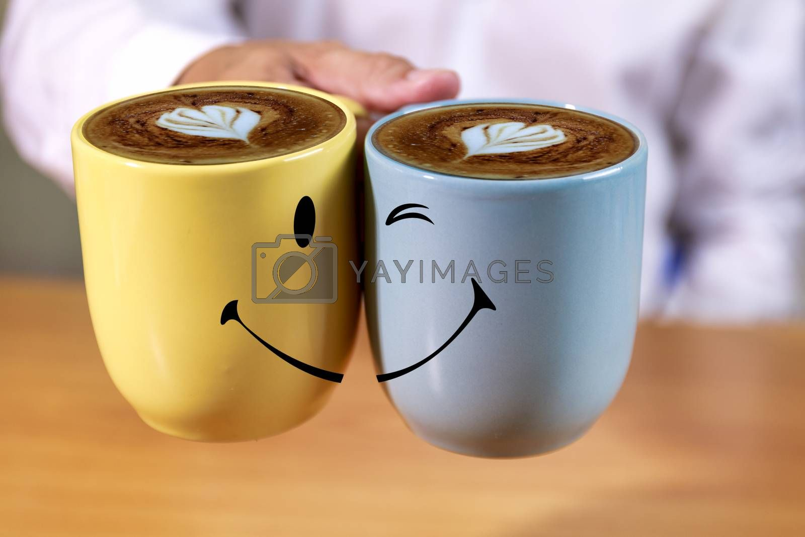 Close up Hand businessman hold coffee cups with smle face background. Hand man hold yellow and blue coffee cups with heart shape creamy and smile background.