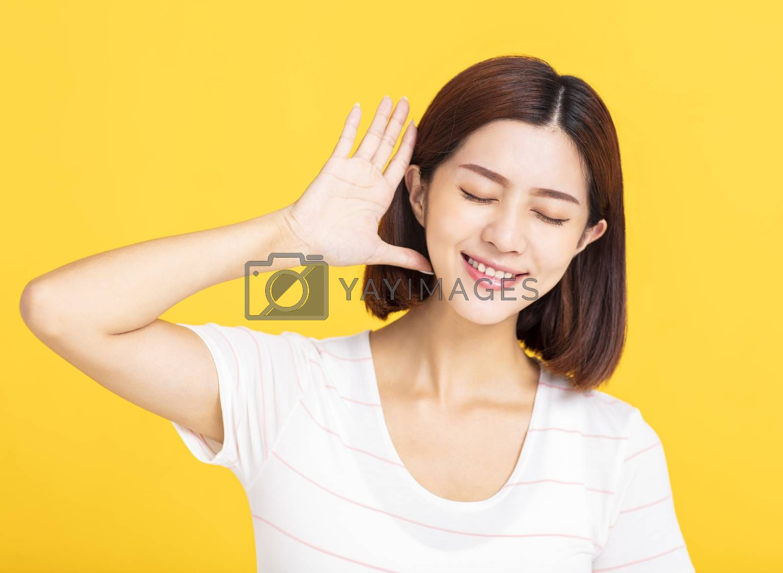 young woman listening to something by putting hand on the ear
