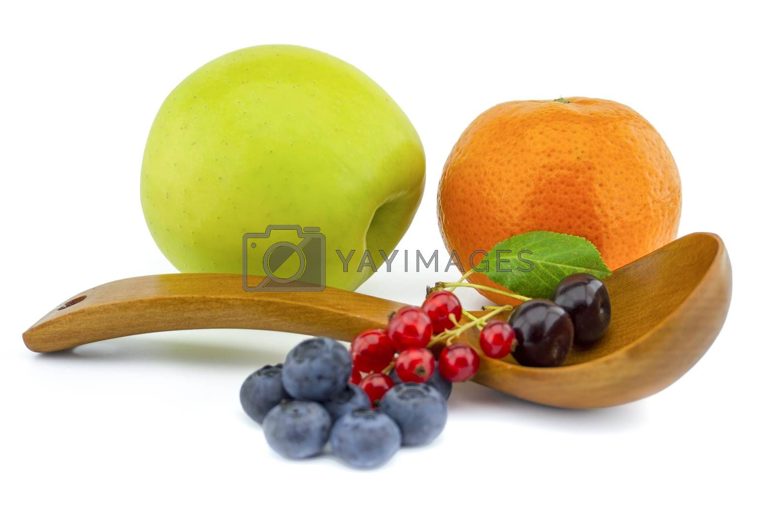 Fresh seasonal fruit still life with assorted berries including blueberries, cherries and red currants on wooden spoons with apple and orange on a white background with copyspace