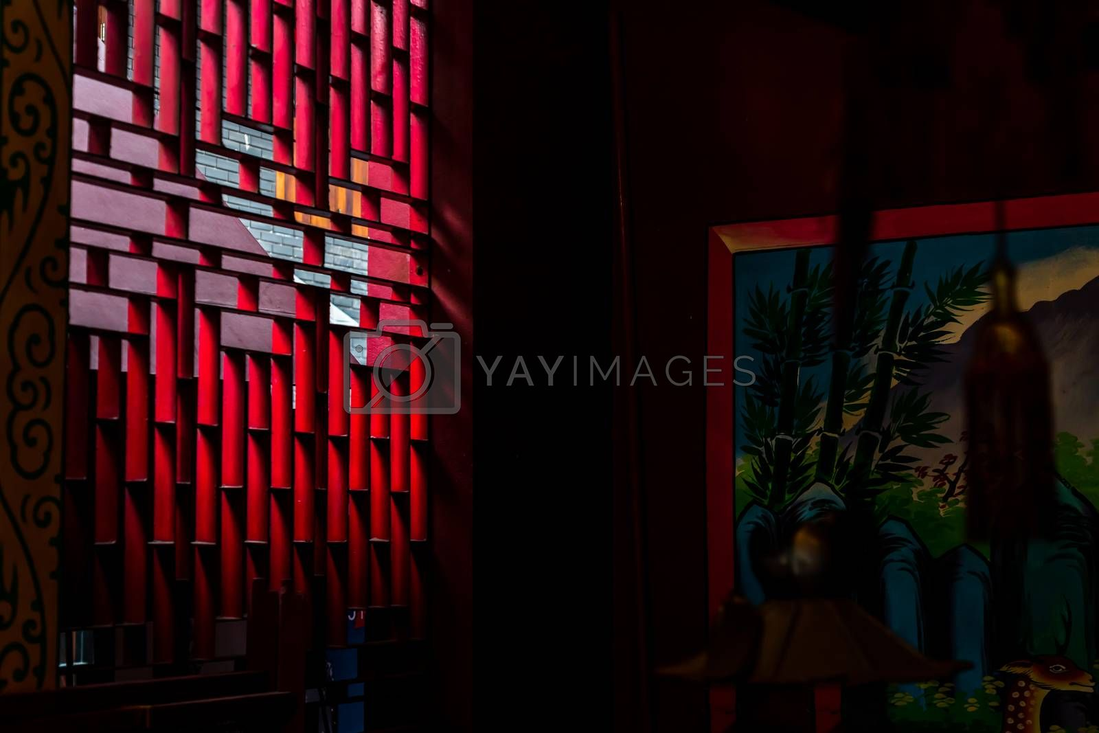 Bangkok, Thailand - Aug 01, 2020 : Light shines through the vent shade in the Chinese shrine's. Selective focus.