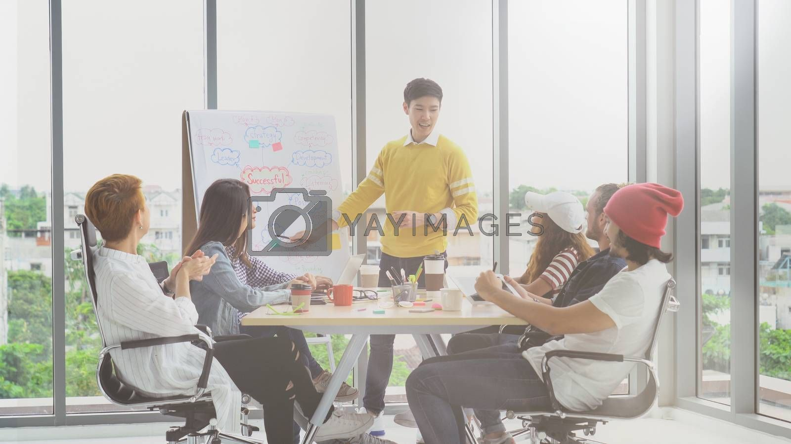 Asian young manager presenting the creative ideas in front of Group Of Asian and Multiethnic Business people with casual suit in happy action in the modern workplace