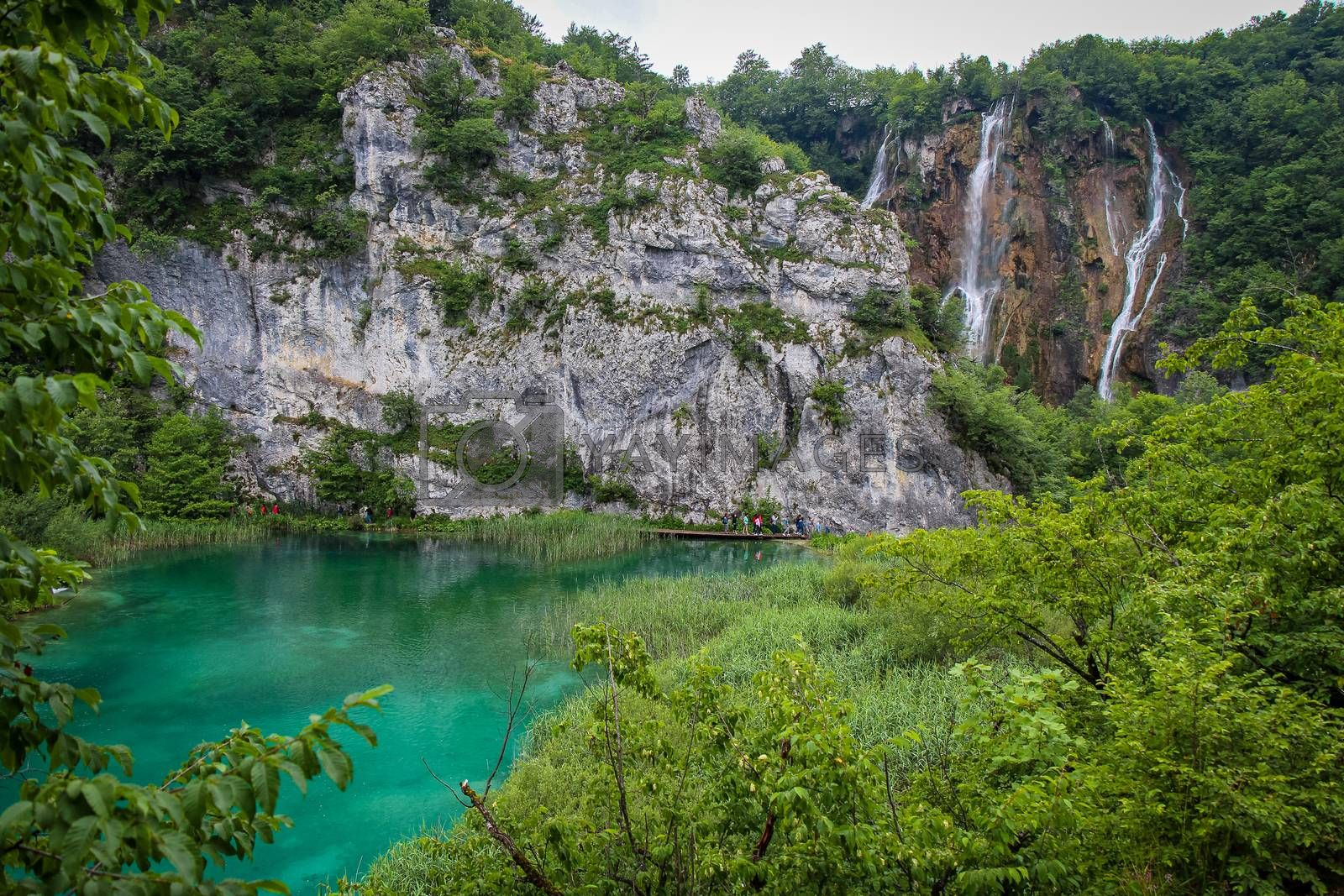A large waterfall flowing over a mountain into a lake at Plitvice Lakes, UNESCO World Heritage Site, Croatia