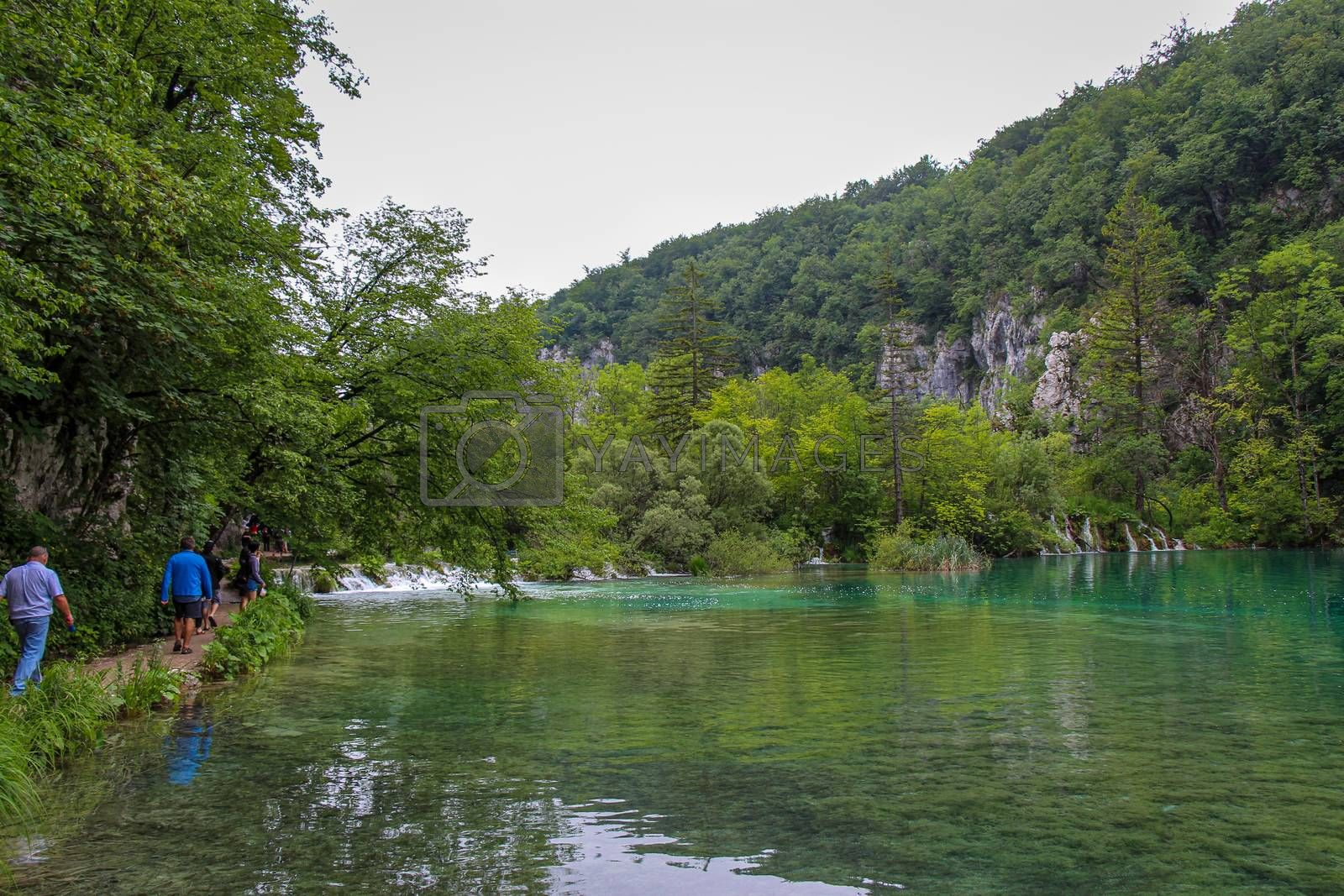 Plitvice Lakes, Croatia - July 14th 2018: Tourists walking along a path by a shallow lake, with waterfalls in the background, at Plitvice Lakes, UNESCO World Heritage Site, Croatia