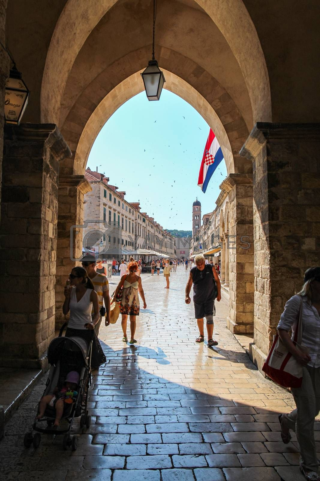 Dubrovnik, Croatia - July 15th 2018: A view down the Stradun main street in Dubrovnik's old town, from an archway, with a Croatian flag flying