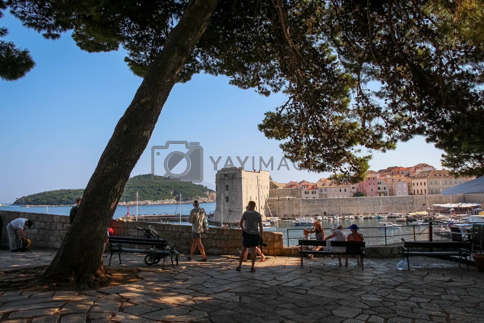 Dubrovnik, Croatia - July 15th 2018: Tourists sitting in the shade viewing the harbour and old town in Dubrovnik, a UNESCO Heritage Site, Croatia