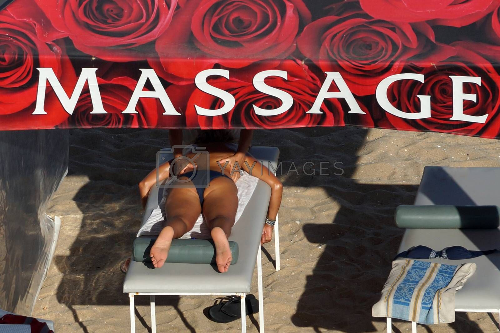 Varna, Bulgaria - August, 16, 2020: Masseuse massages woman in tent on the beach