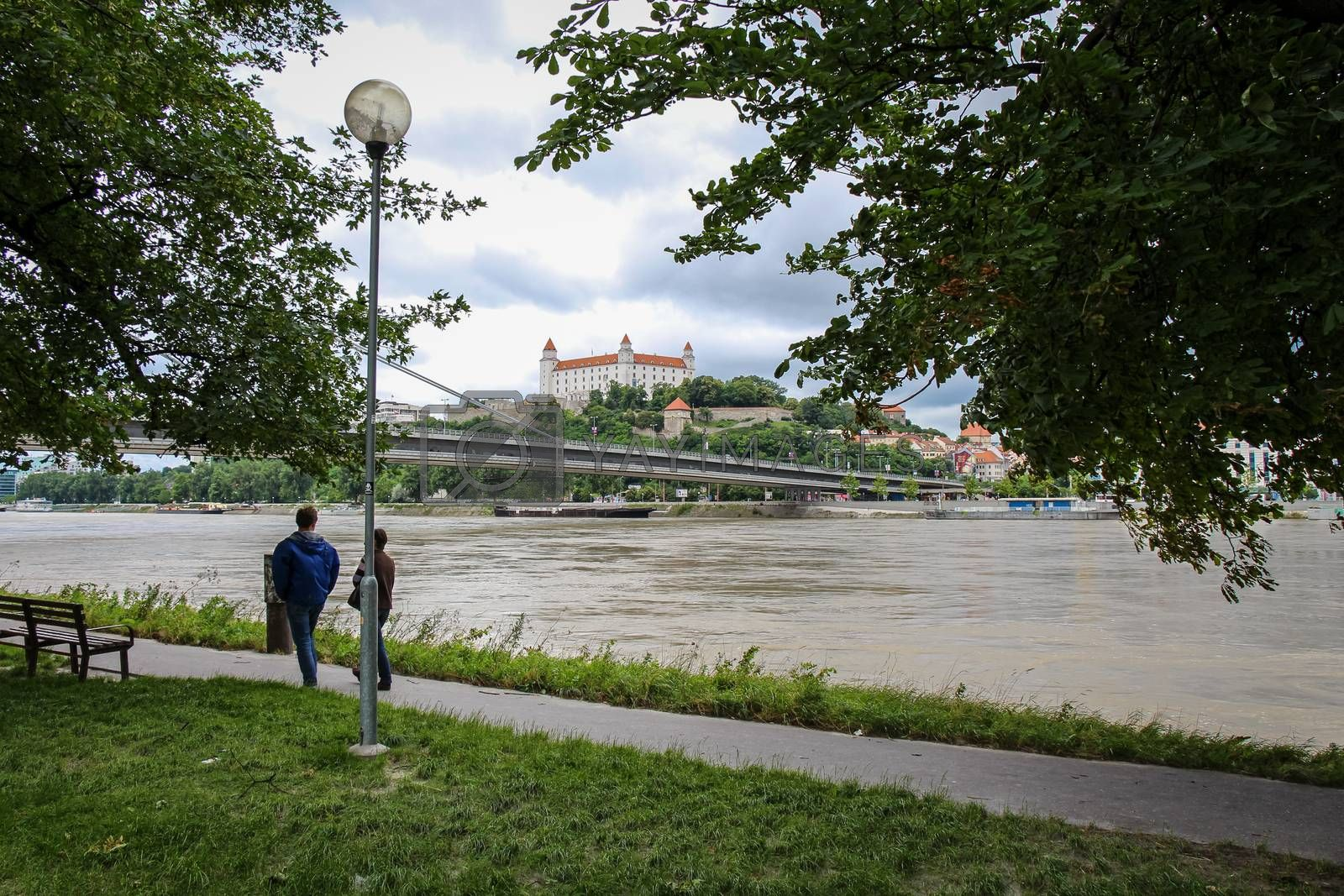 Bratislava, Slovakia - July 5th 2020: People walking along a footpath by the River Danube in Bratislava, with the Castle on the hill in the background, Slovakia