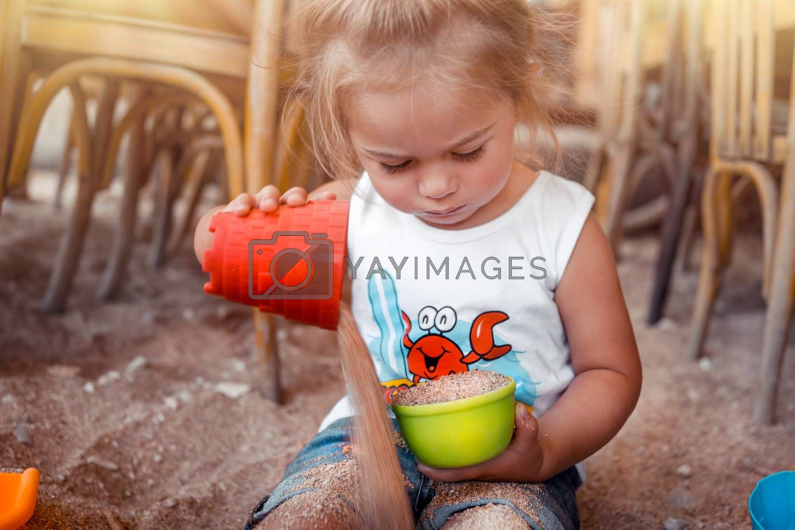 Portrait of a Little Blond Baby Boy Playing with Small Colorful Plastic Sand Toys. Summer Holidays on the Beach. Building a Sandcastle.