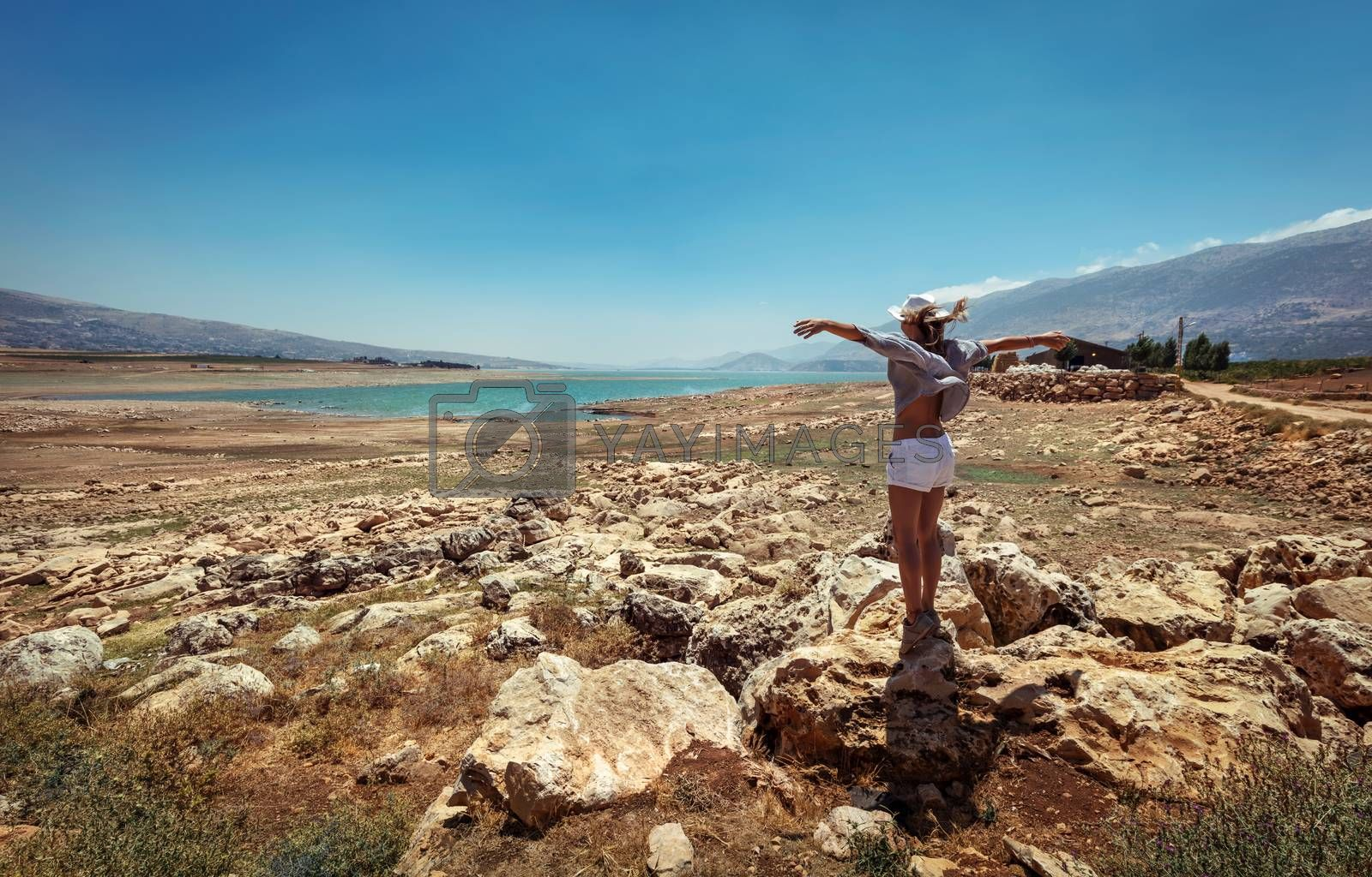 Happy Woman with Raised up Hands Standing Near Lakes and Enjoying Amazing View. Beautiful Stony Landscape in the midst of Valley. Travel Along Lebanon.