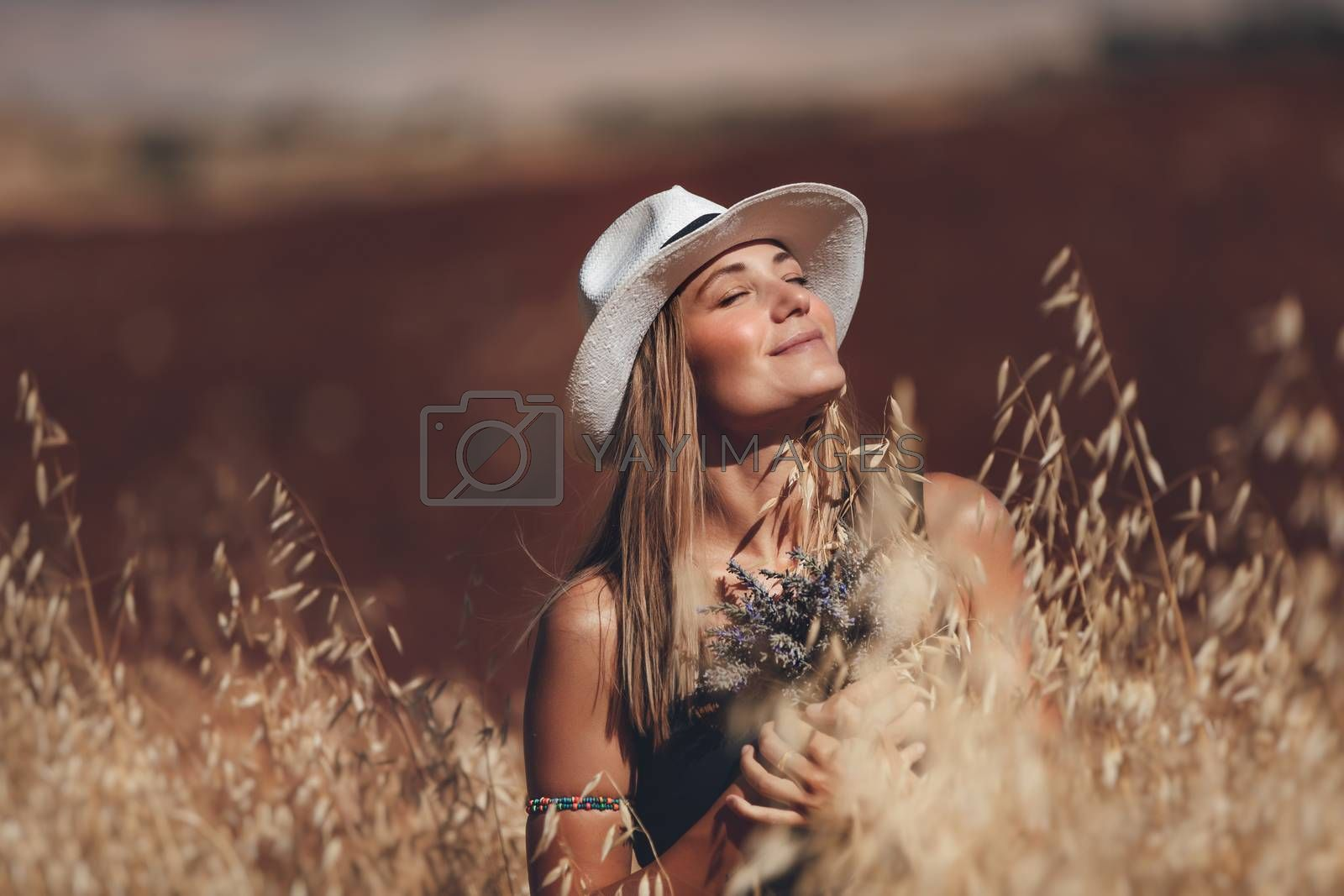Portrait of a Happy Young Blond Woman Outdoors. Girl Holding Lavender Flowers Bouquet. Standing in a Wheat Field. Enjoying Nature. Beautiful Sunny Day.