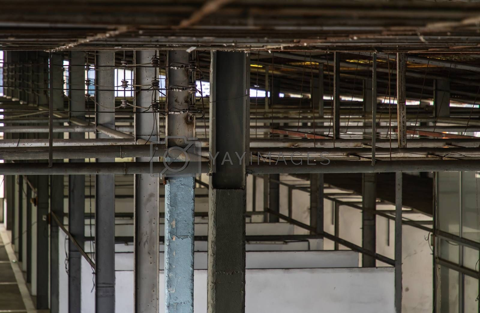 The structure inside the warehouse with light pole. Old structure in old building indoor. Selective focus.