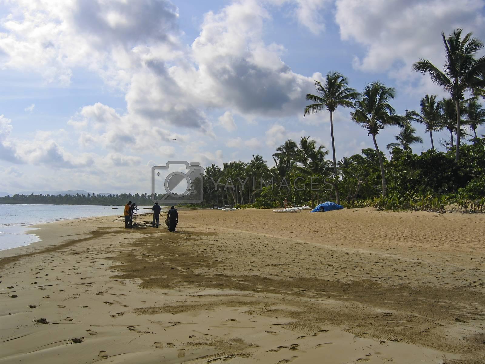 Locals clean the beach at Samana