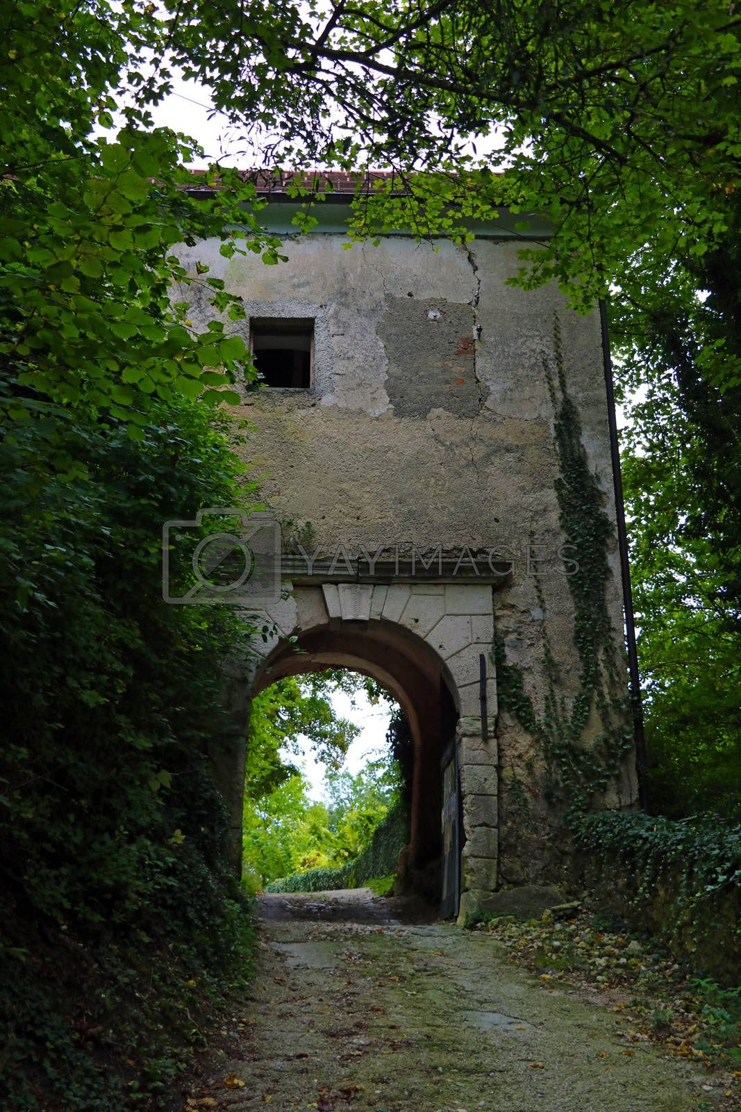An old building with an arch for car passage