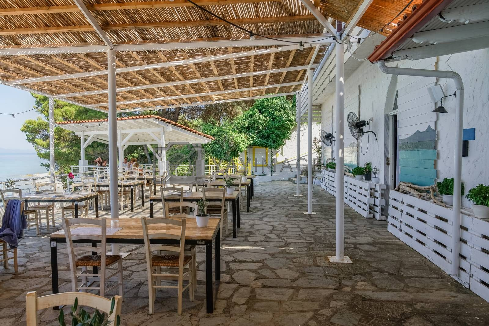 Restaurant outdoor seating area by the sea with a few customers in Kryopigi, Kassandra peninsula.