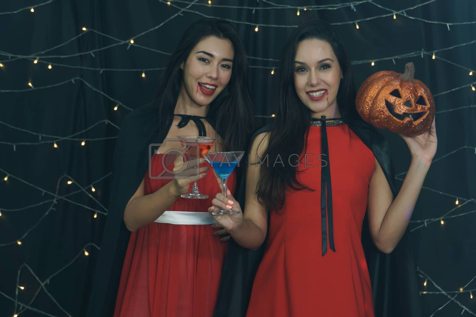 Beautiful woman and friend in Halloween devil costume with carved pumpkin and drinking cocktail. Have fun at a party in nightclub decorated with lights. Halloween celebration