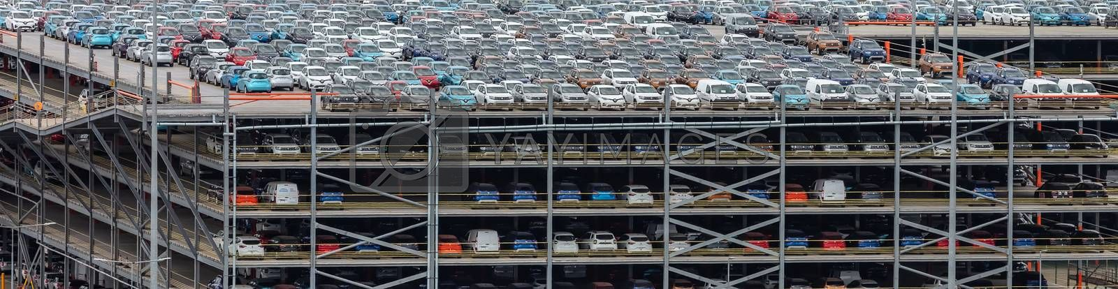 Southampton port, England, UK - June 08, 2020: Multilevel parking lot, storage facility in the port of Southampton. Full of various imported cars. Aerial view.