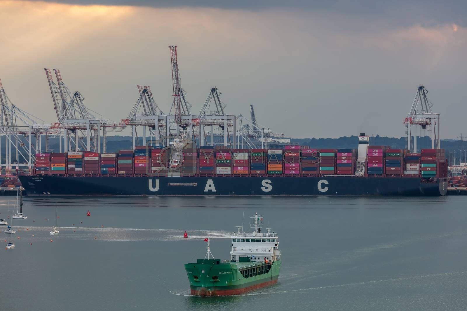 Southampton port, England, UK - June 08, 2020: Aerial view of Southampton port. Sunset. Massive container ship UASC being loaded in the background. Arklow Rogue ship sailing in the foreground.