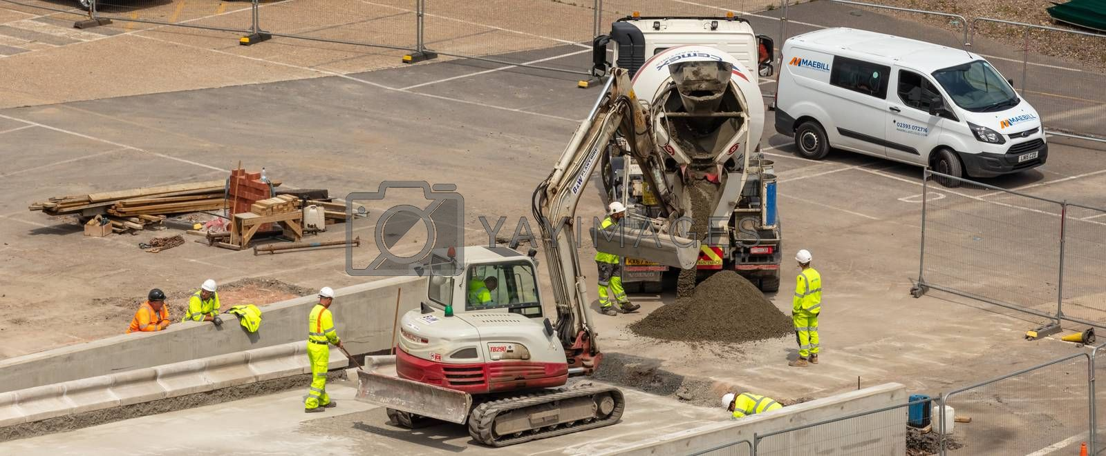 Southampton port, England, UK - June 08, 2020: Construction workers wearing light green safety clothing and hard hats on site. Excavator, concrete mixer. Construction concept.
