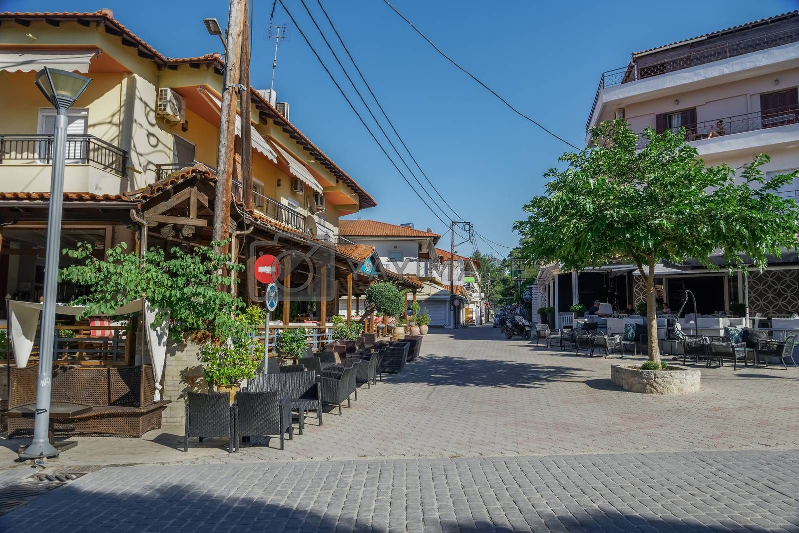 Day outdoor seating area with a few customers at Hanioti village square, Kassandra peninsula.
