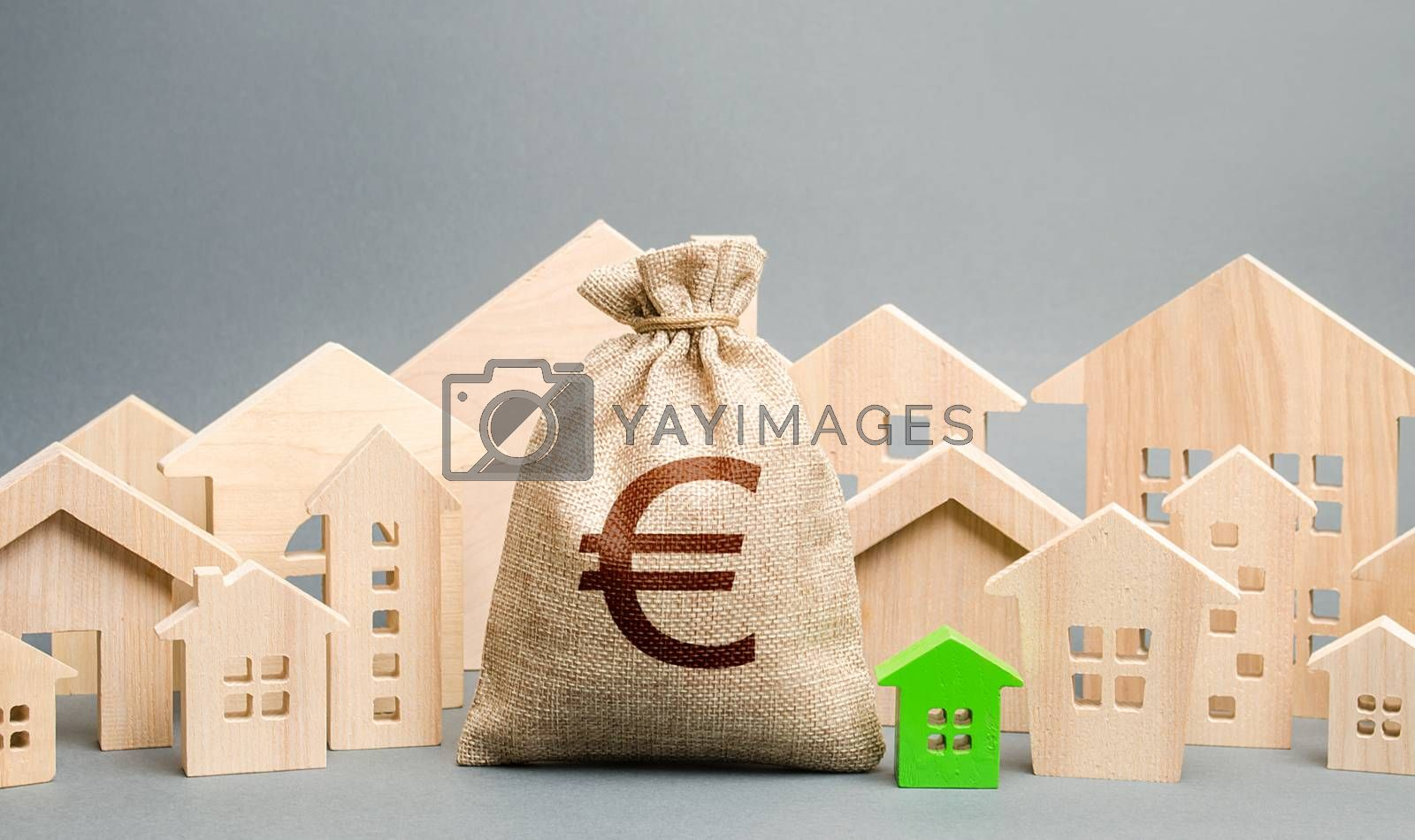 Euro money bag and a city of house figures. Buying real estate, fair price. City municipal budget. Property tax. Development and renovation of buildings. Investments. Cost of living in town.