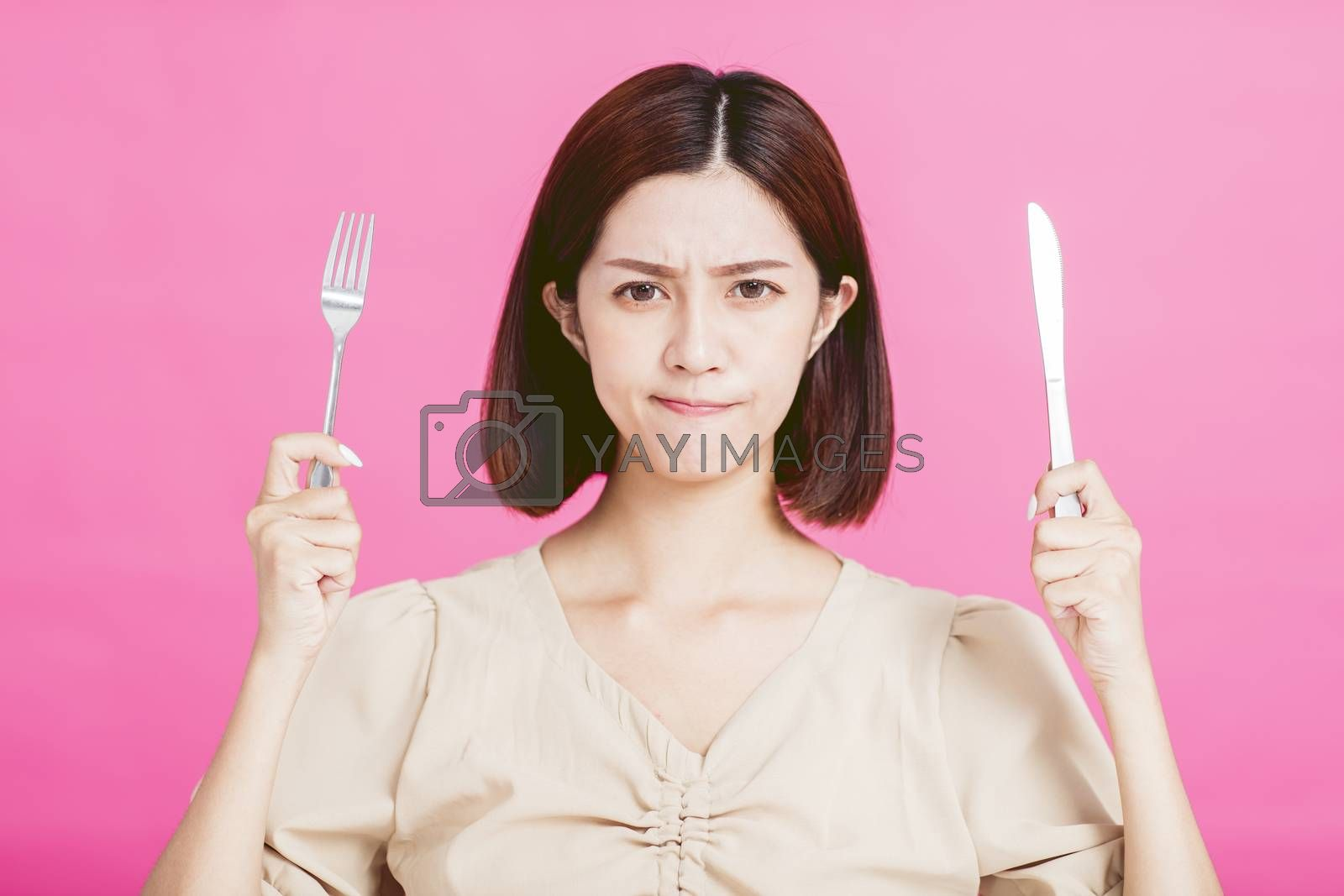 angry young woman holding a fork and  table knife with tasting food concept