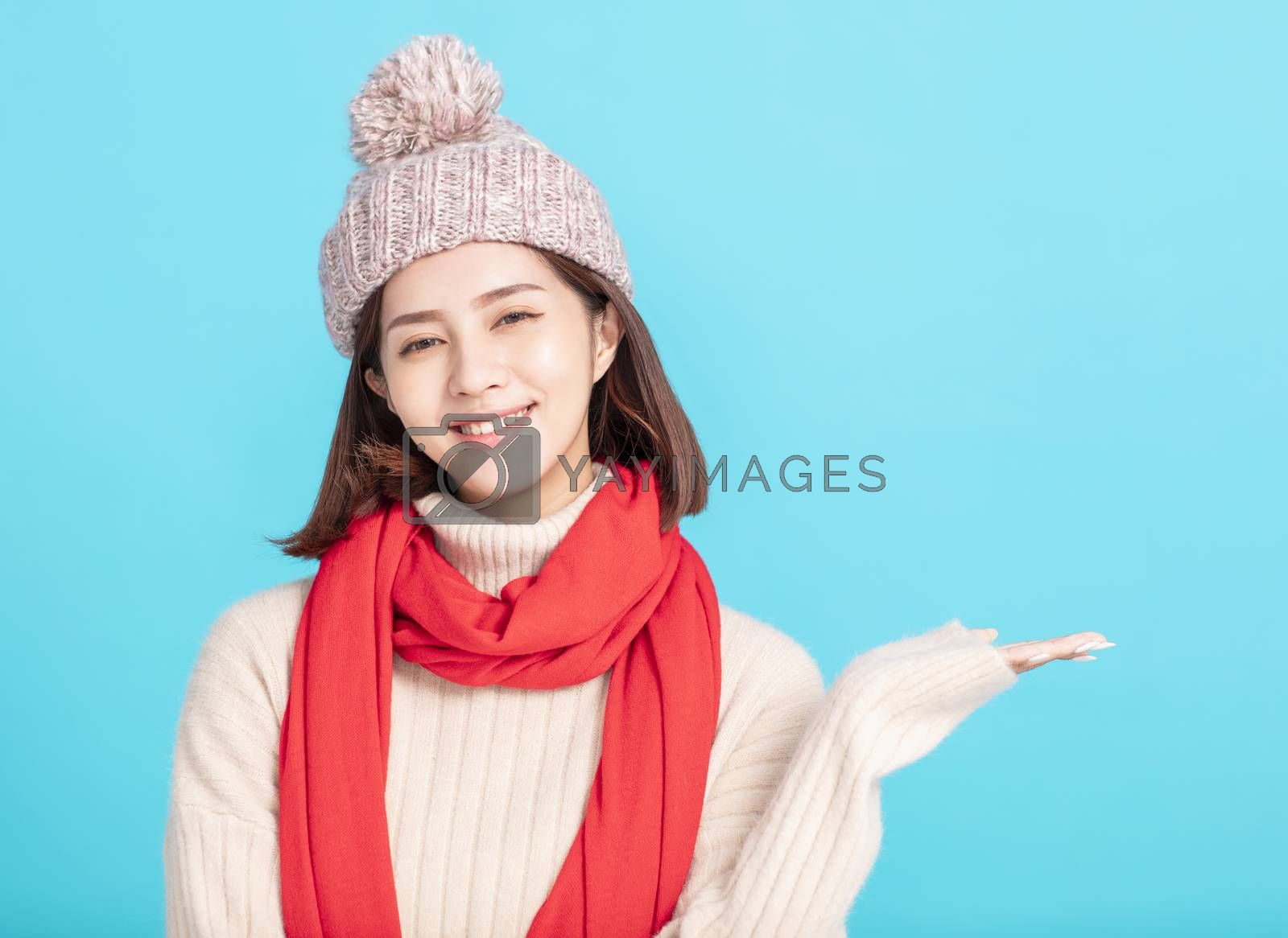 happy young asian woman wearing stylish warm clothes and hand showing something