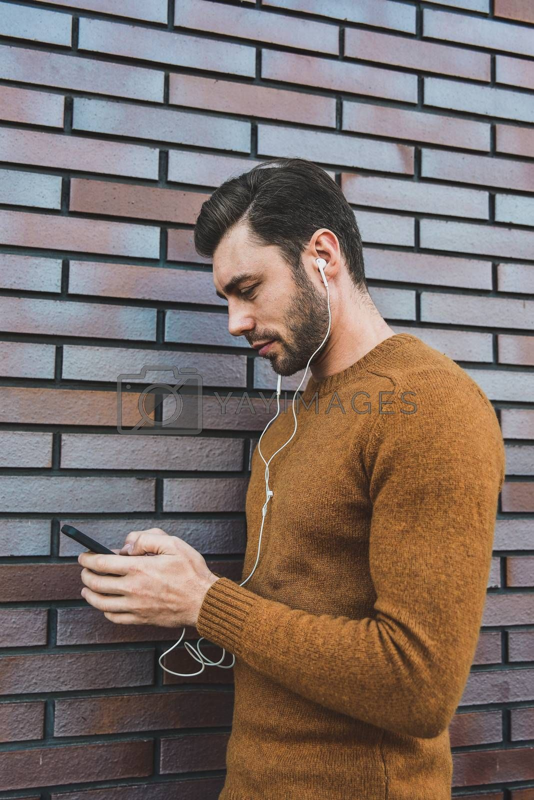 Smiling man listening to music on headphones and leaning against brick wall.