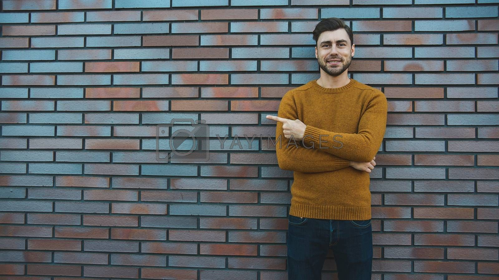The horizontal look of an attractive young man who advertises something new, points his finger to the side, stands against a brick wall. People and lifestyle