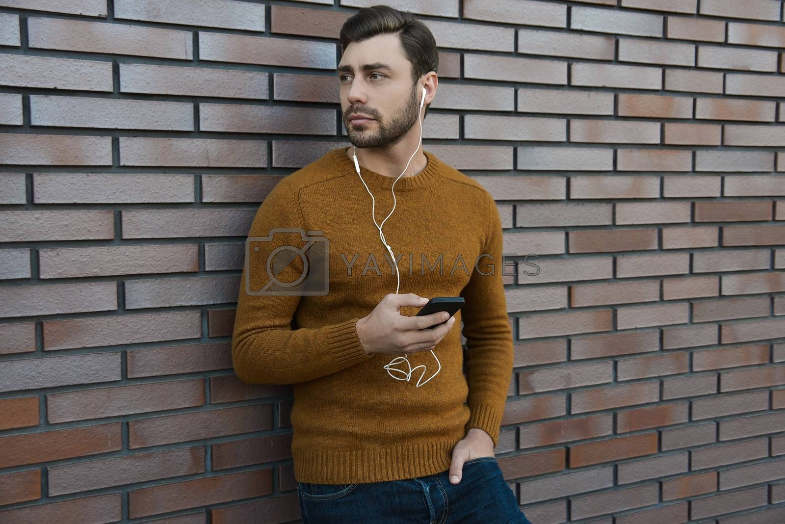 Amazing man holding smartphone in smart casual wear standing.