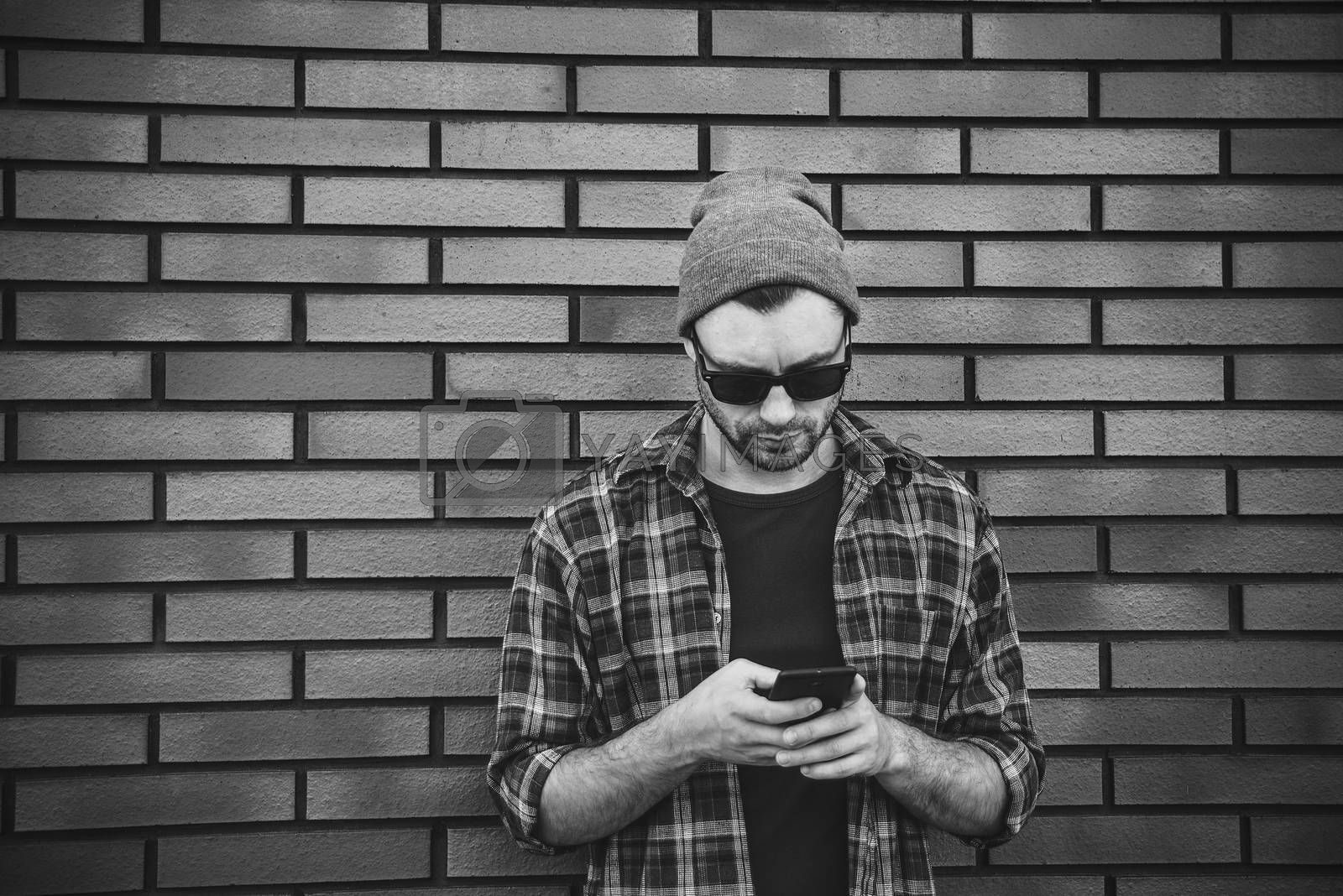 Hipster sms texting phone app in city street on brick wall background. Amazing man holding smartphone in smart casual wear standing.