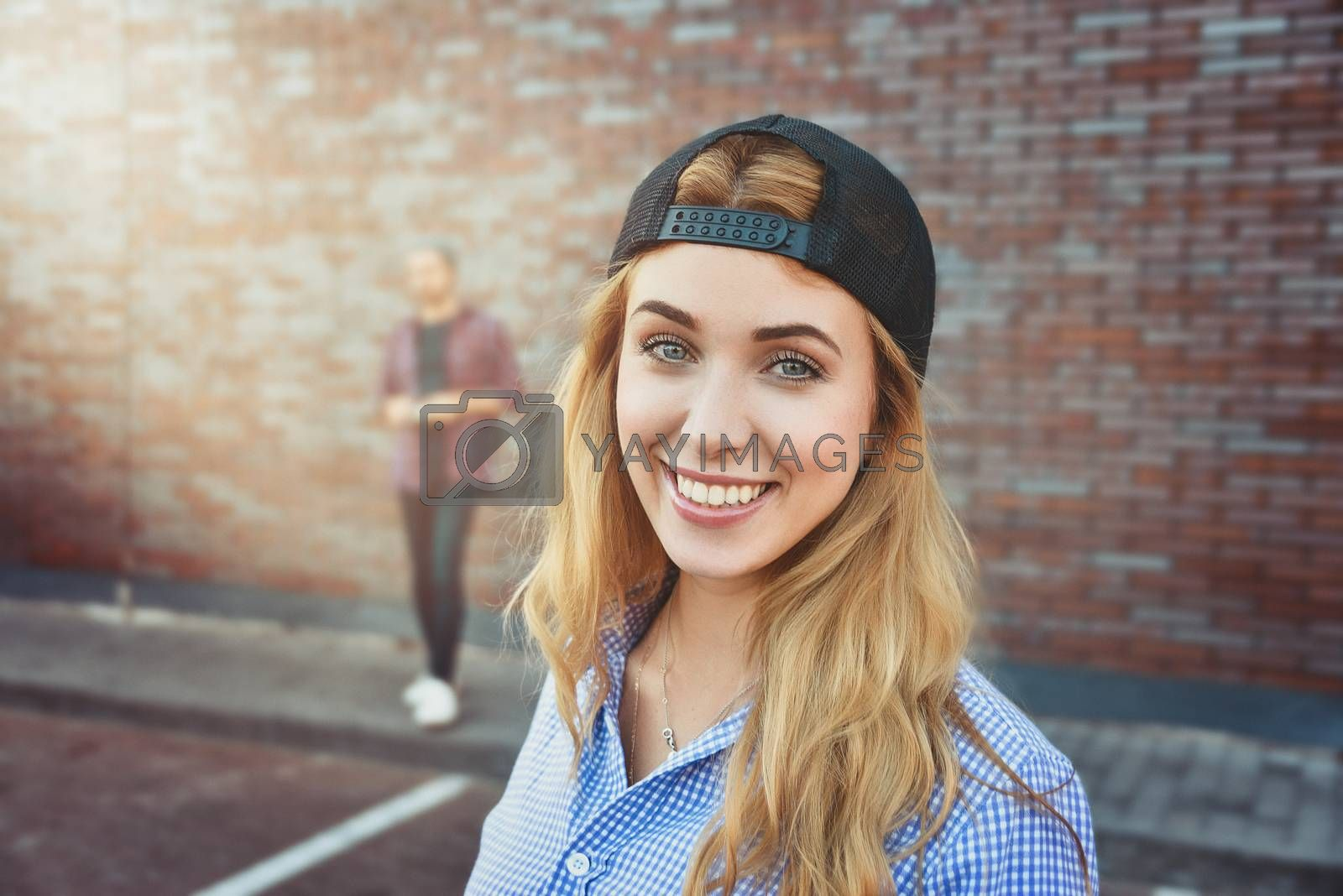 Pleased Caucasian teenage girl wears black cap and shirt, going to have stroll with friends, poses against white background. Youngster woman dressed in fashionable clothes.