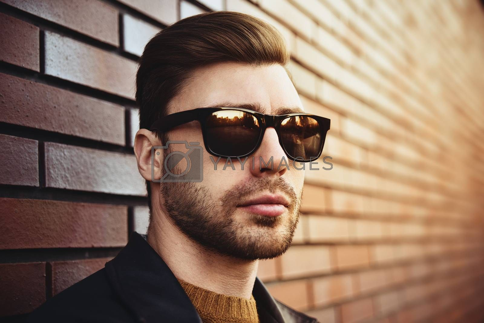 Portrait of stylish handsome young man with bristle standing outdoors and leaning on brick wall.