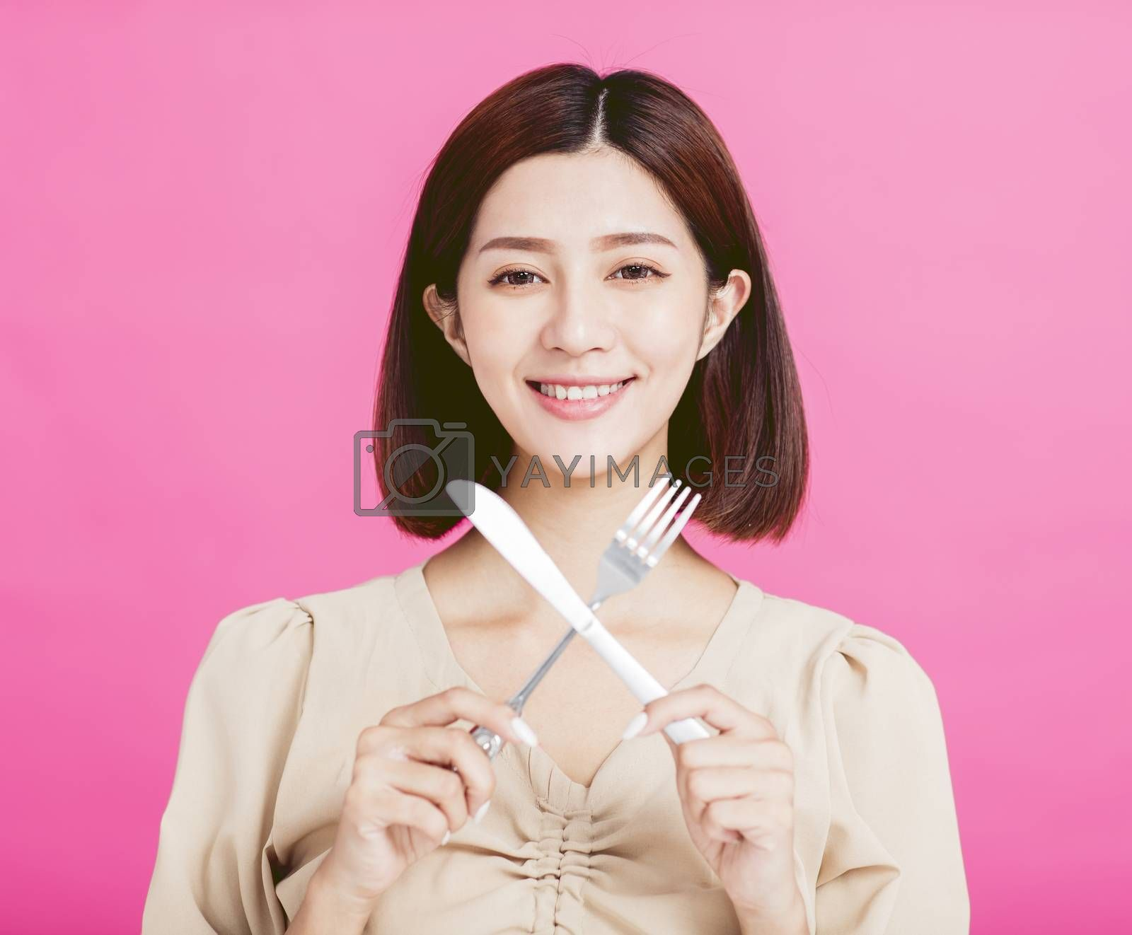 Beautiful young woman holding a fork and  table knife with tasting food concept