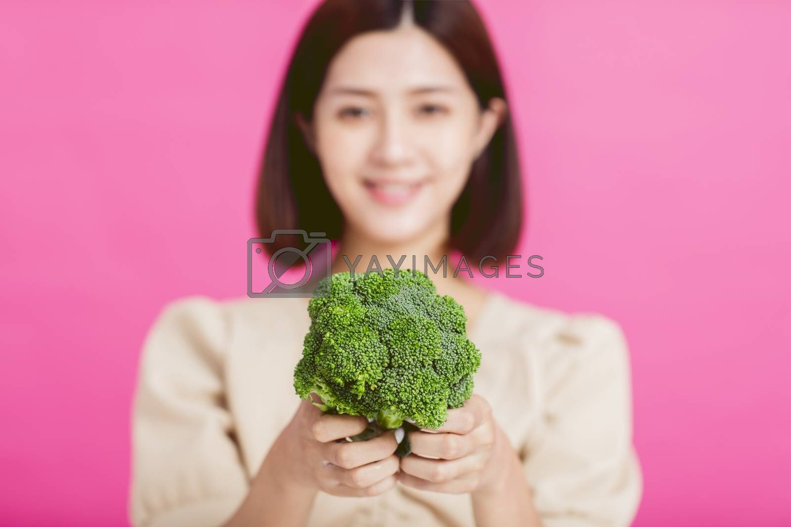 Healthy young woman showing green food