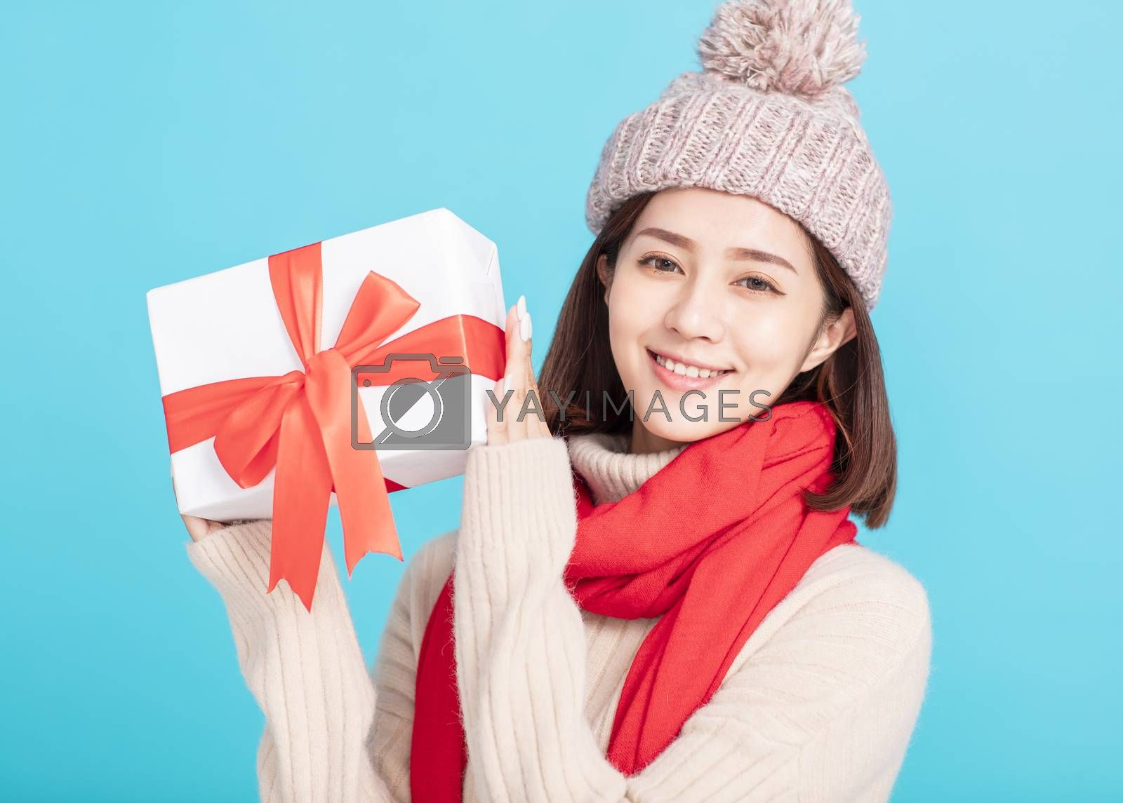 young woman in winter dress and showing giftbox