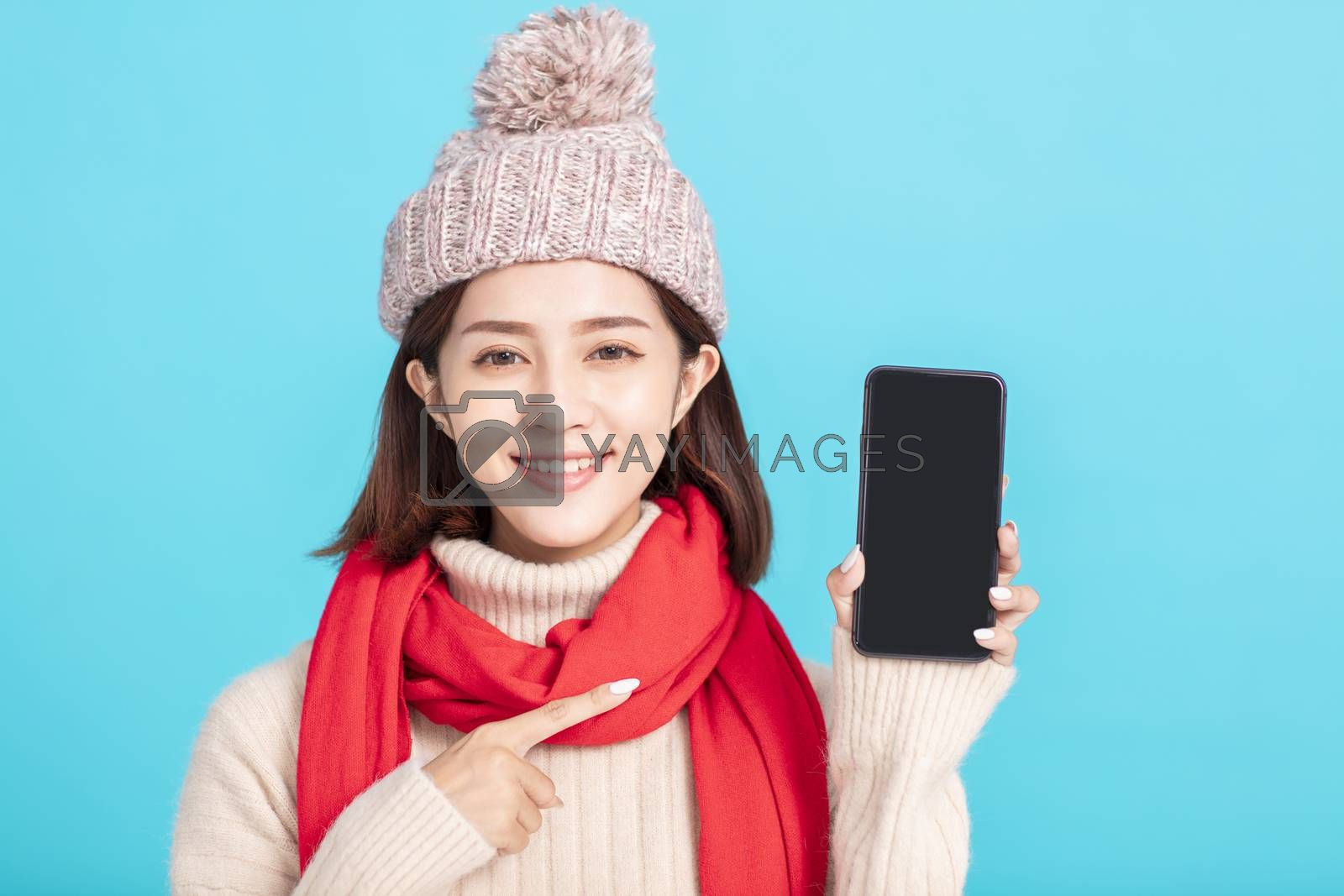 Smiling young woman in winter dress and showing  smart phone