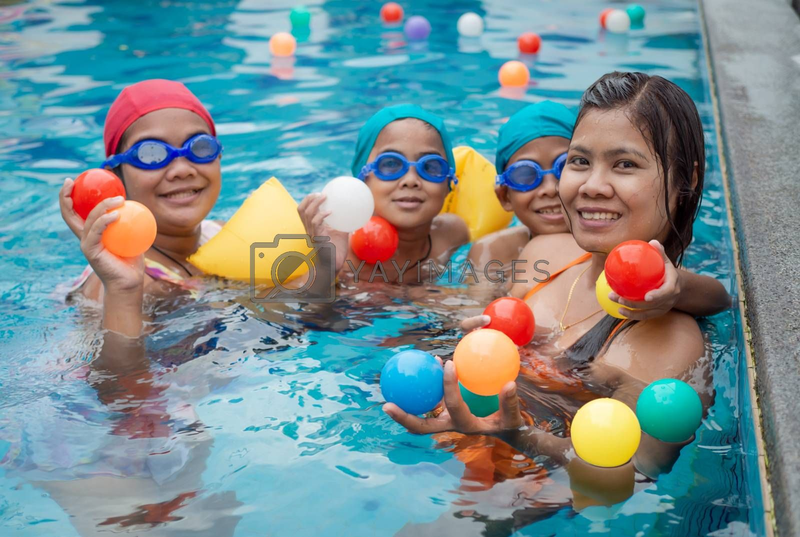 A portrait of a mother and her children playing ball in the pool.