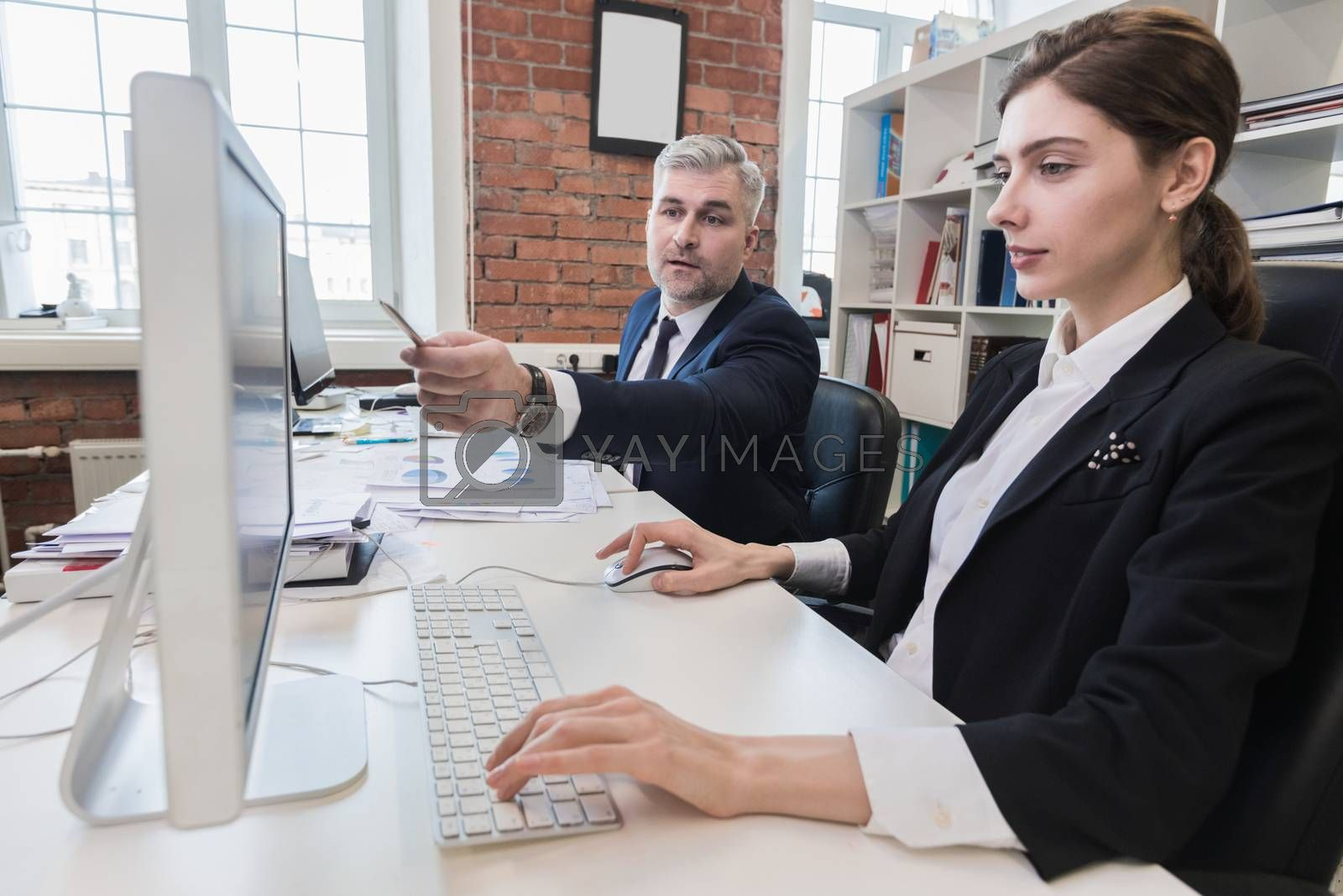 Business people working at office together, financial data, statistics, paperwork, Man pointing at computer monitor