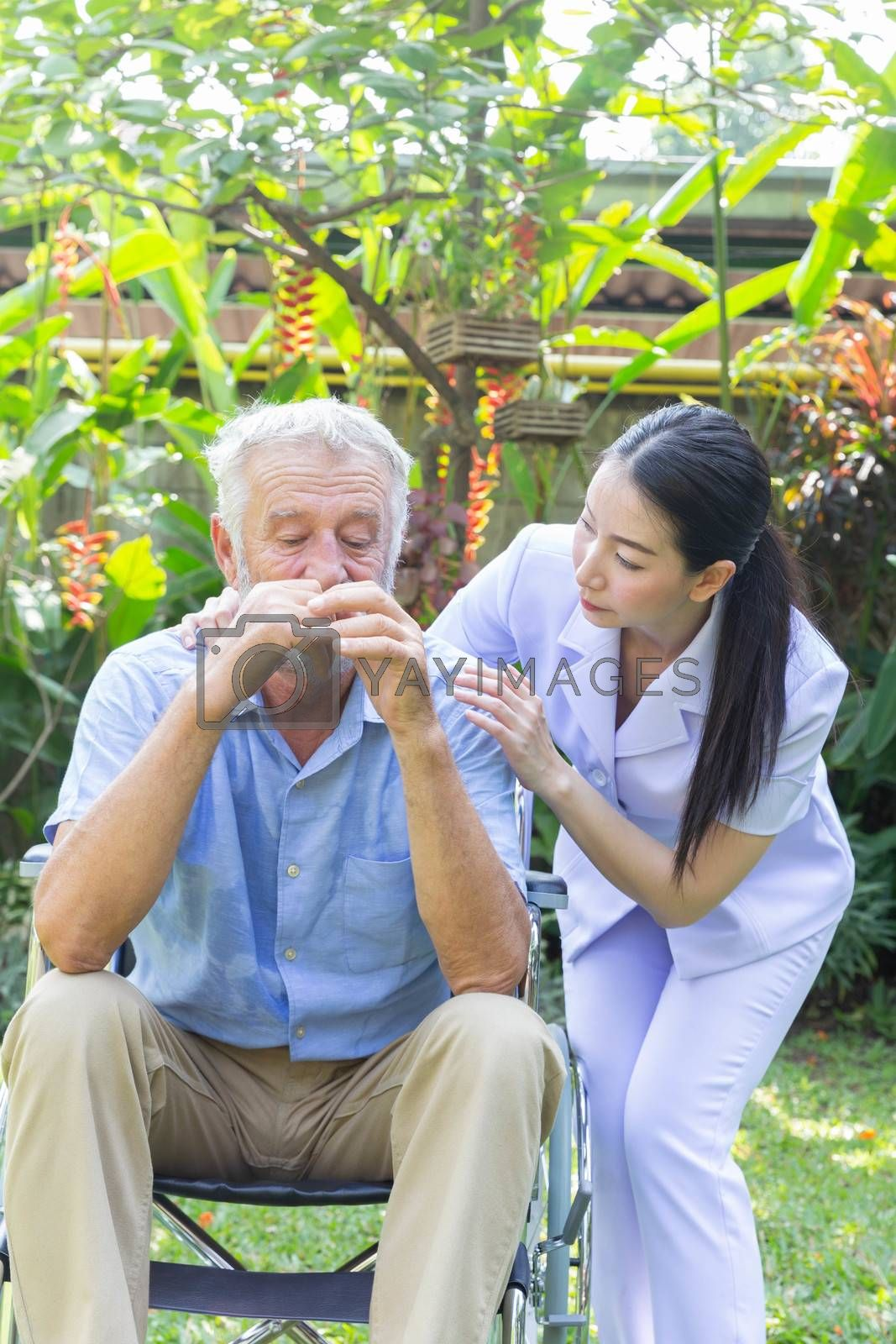 Nurse take care a depressed thoughtful senior retirement man on his wheelchair in a garden in his home