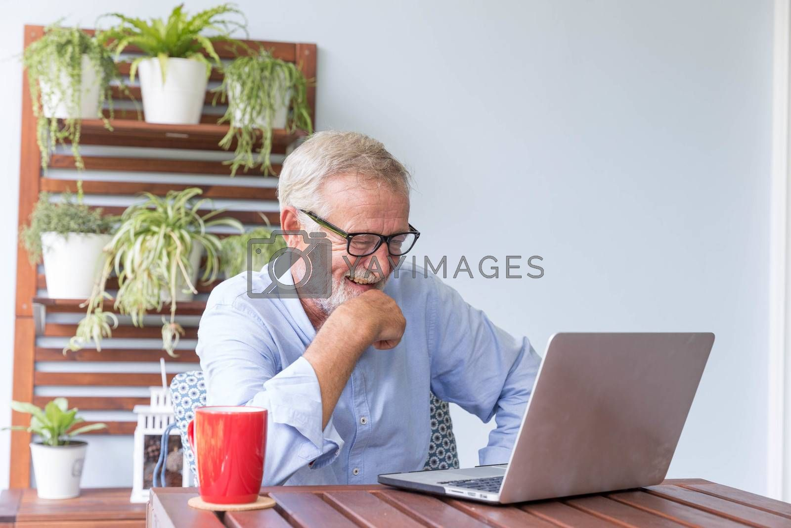 Senior retirement man is enjoy chating with someone using his laptop at home and feeling happy