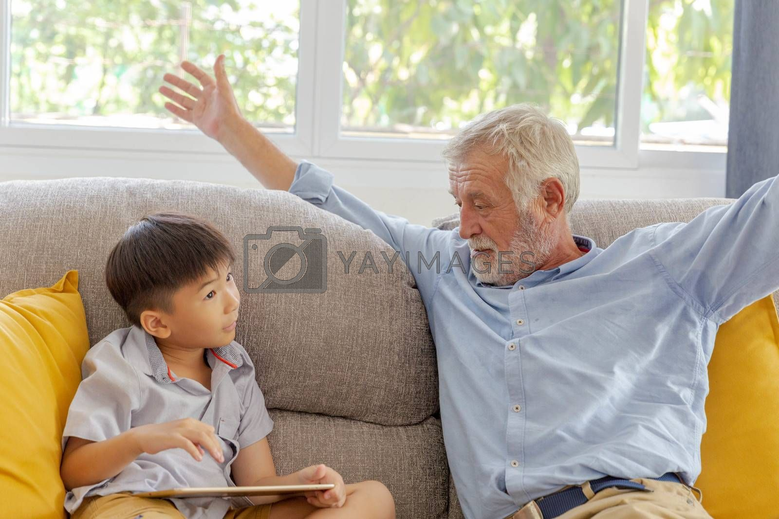 Grandfather and little cute grandson playing touchscreen tablet PC together on sofa in their house