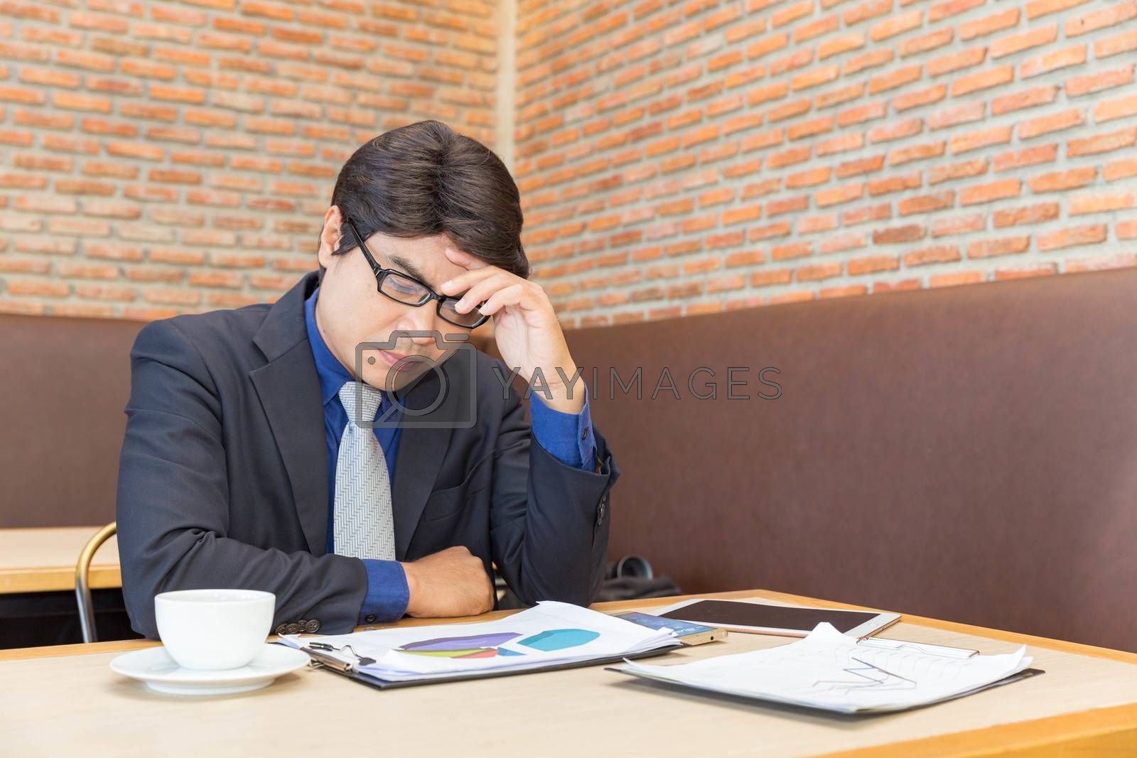 Stress businessman sitting on his desk and worry about his business