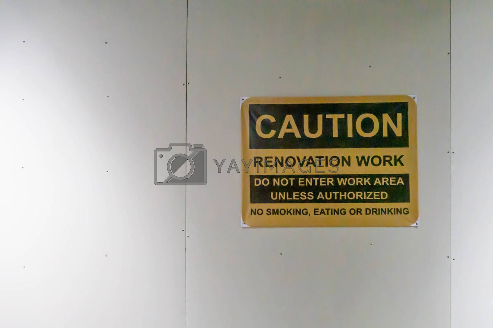Caution sign board posted on wall for indoor renovation work