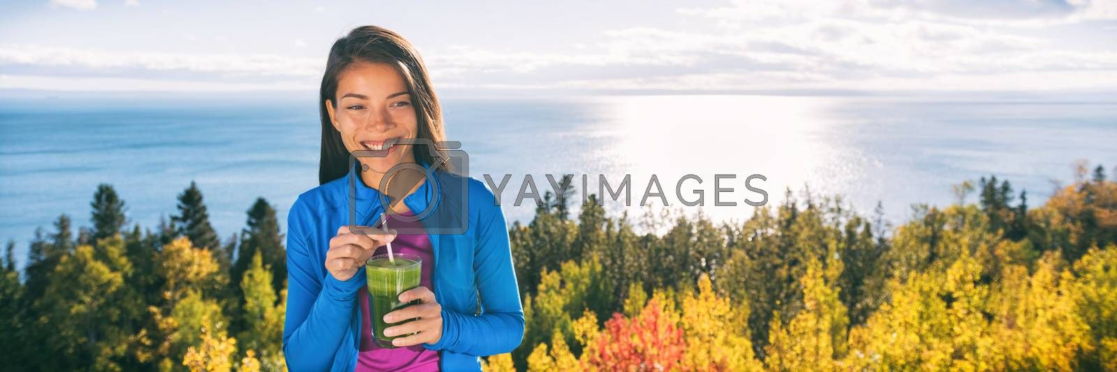 Outdoor fall nature Asian woman drinking fresh green vegetable smoothie as a healthy breakfast or lunch detox on home terrace in beautiful morning nature outdoors. Happy smiling fitness girl.