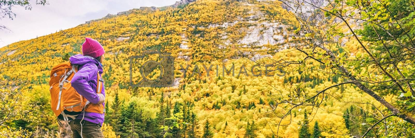Woman hiker hiking in trail autumn nature panoramic banner. Girl relaxing looking at scenic view of fall mountain landscape . Adventure travel outdoor person near river during nature hike in autumn.