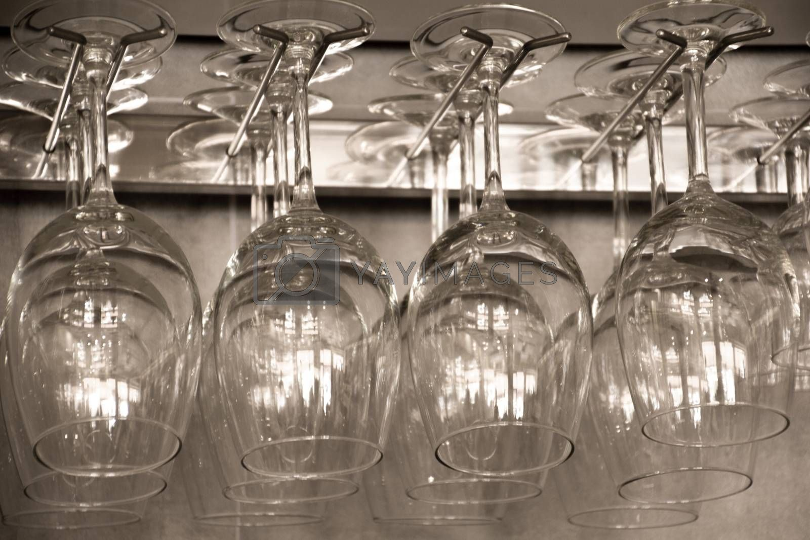 some glass cups hanging from a metal hook upside down
