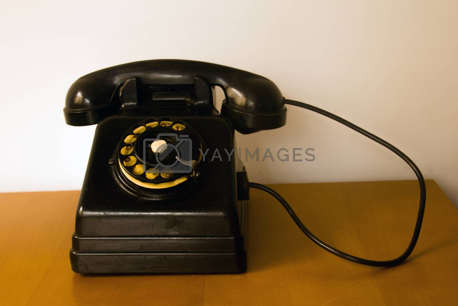 old telephone with rotating disc placed on a furniture